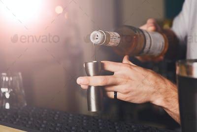 Barman's hands making shot cocktail