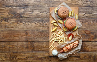 Fast food top view on wood. Hamburger, hotdog and fries