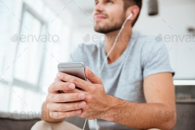 Happy man listening music. Focus on hands and phone