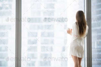 Young woman looking through the floor window