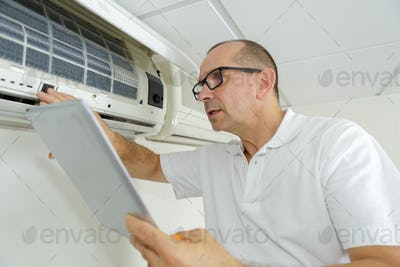 man checking airconditioning manual while using it