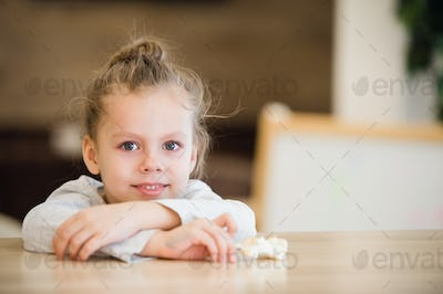 Beautiful calm little girl sitting at wooden table