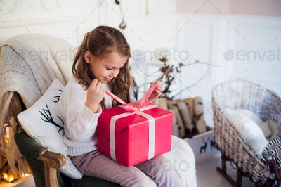 Little girl holding a Christmas gift box. Cute kid sitting on the chair and unpacks xmas presents