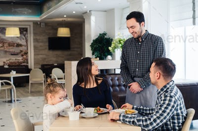 Waiter serving family in a restaurant and bringing full plate