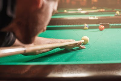 Man trying to hit the ball in billiard.
