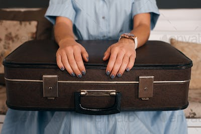 Female hands  putting on luggage.