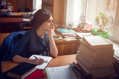 Serious woman thinking in library silence.