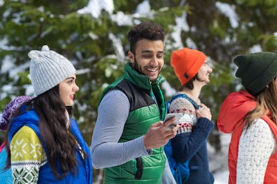 Hispanic Man Using Smart Phone Chatting Online Snow Forest Young People Group Walking Outdoor Winter