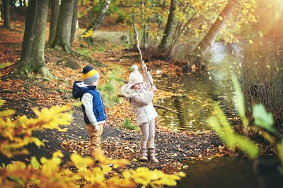 Two children playing with branch near pond