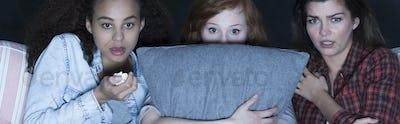 Terrified girls watching scary movie