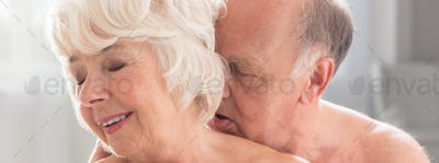 Elderly naked woman kissing with passion