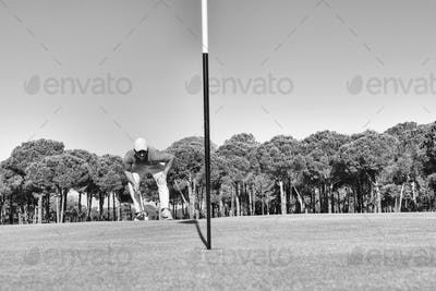 golf player hitting shot with club on course