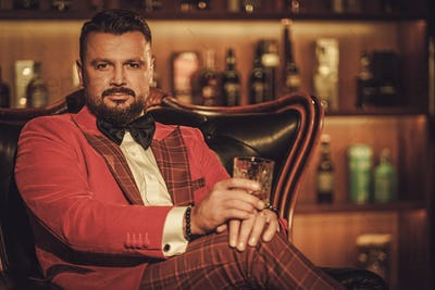 Extravagant stylish man with whisky glass sitting on armchair in