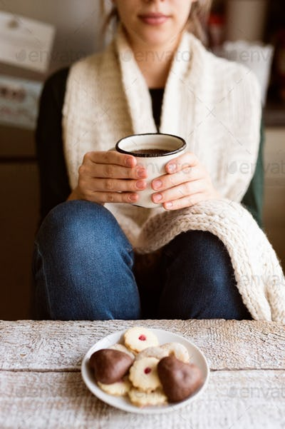 Unrecognizable woman with white knitted scarf holding coffee cup.