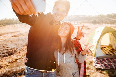 Young couple making selfie while standing at campsite