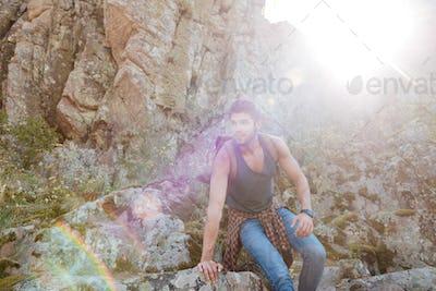Young traveling man walking on rock