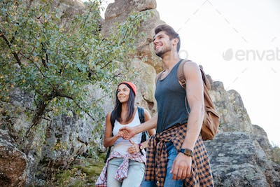 From below image of couple walking on rock