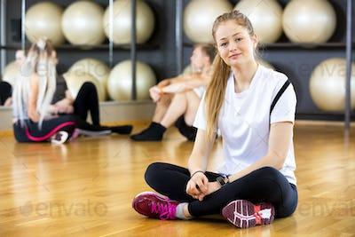 Confident Woman Sitting Cross Legged In Fitness Center