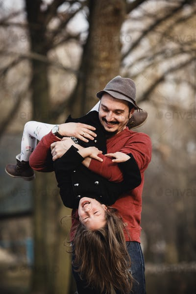 Dad holding his daughter upside down