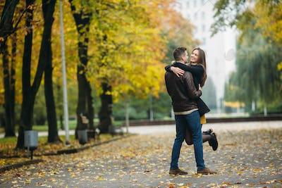 attractive happy couple walking in autumn park