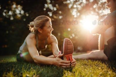 Beautiful young woman exercising at park with man