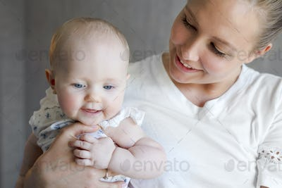 Smiling cute baby girl with her caring mother