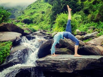 Woman doing yoga asana at waterfall
