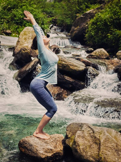 Sorty fit woman doing yoga asana Utkatasana outdoors
