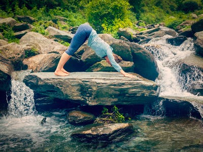 Young sporty fit woman doing yoga oudoors at tropical waterfall