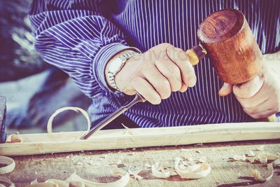 hands of the craftsman carve a bas-relief with a gouge. Craftsma