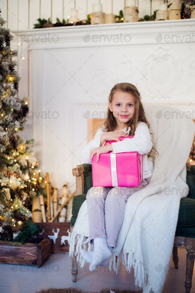 Beautiful girl near Christmas tree unpacking presents sitting on a chair