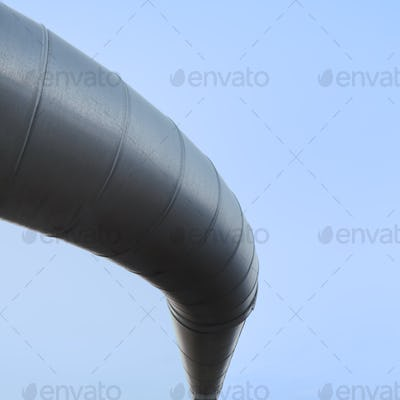 Curved industrial pipe line, sky background. Geothermal power plant.