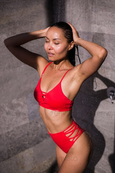 A young sexy woman wearing red swimsuit showering outside at luxury hotel