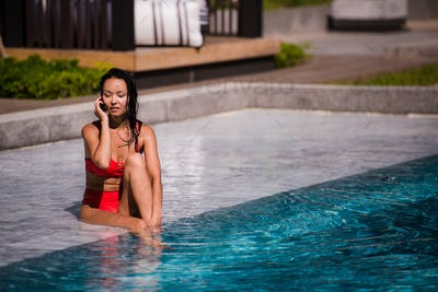 Calling all her friends to join. Portrait of a happy young woman sitting by the pool talking on her