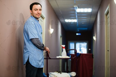 A man who is on the hotel cleaning crew staff is smiling with a towel vacuum in the process of