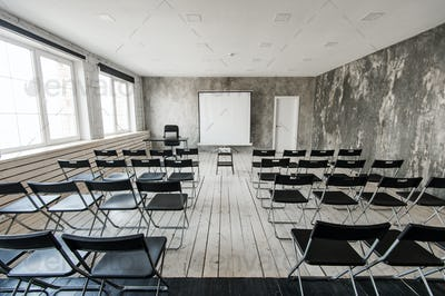 Empty modern classroom with black chairs projector screen