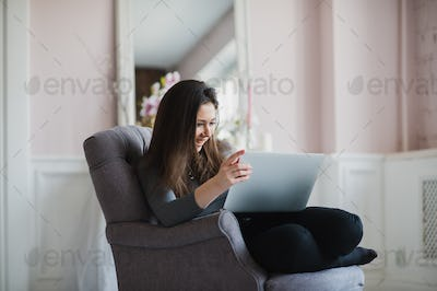 Pretty lady working on her laptop while sitting in an armchair