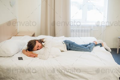 A woman laying on her bed still dressed in her clothes to tired to get in the bed.