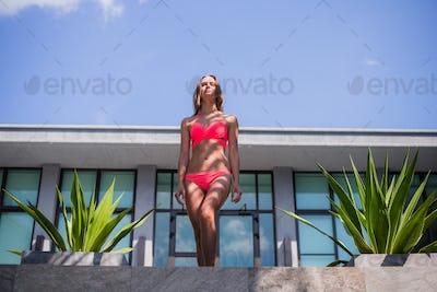young sexy beautiful woman in pink bikini, posing on terrace of resort hotel, slim, tanned skin