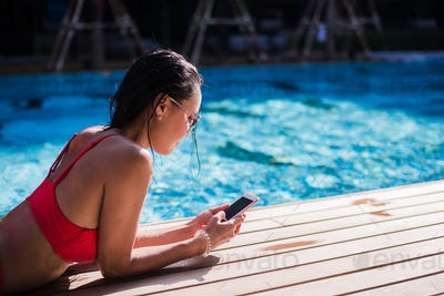 Beautiful woman leaning on poolside and typing a text message on cellphone