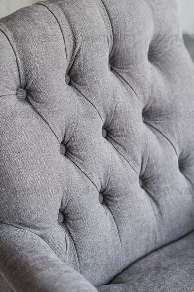 Seamless background texture close up of a grey sofa back with button detail on a thick cloth.