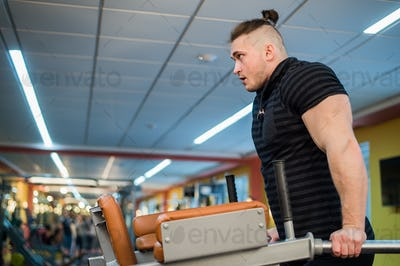 Focused man doing dips in the gym