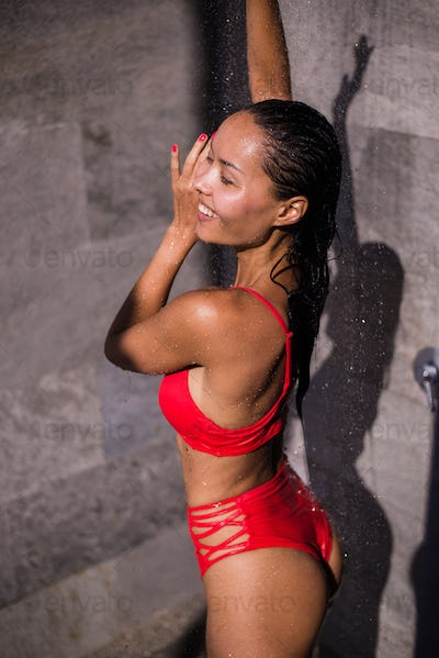 Sporty young beautiful sexy woman in a red swimsuit taking refreshing shower after swimming in the
