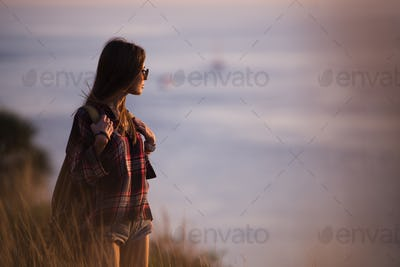 Woman traveler looks at the edge of the cliff on the sea bay of mountains in the background at