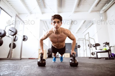 Young fit hispanic man in gym doing push ups on kettlebells