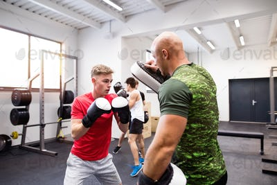 Handsome fit young man in gym boxing with his trainer.