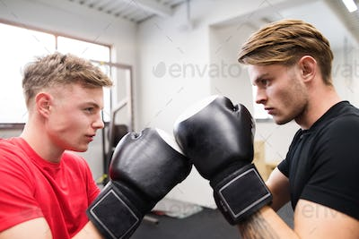 Two fit handsome men in gym boxing.