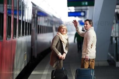 Senior couple on train station pulling trolley luggage, waving.