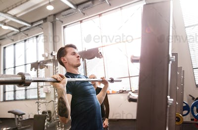 Fit young man in gym working out, lifting barbell