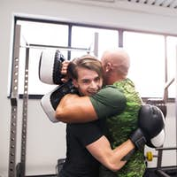 Fit hispanic man in gym boxing with his trainer, hugging.